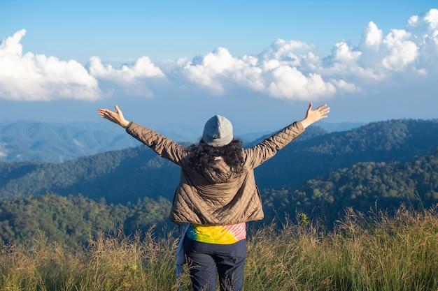 행복 한 여자의 후면 안개와 구름보기를보고 최고 산에 서 서.