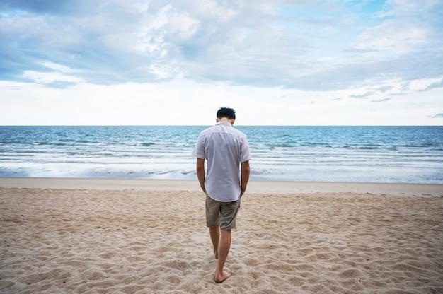 바다에서 해변을 걷는 흰 셔츠에 외로움 남자의 후면