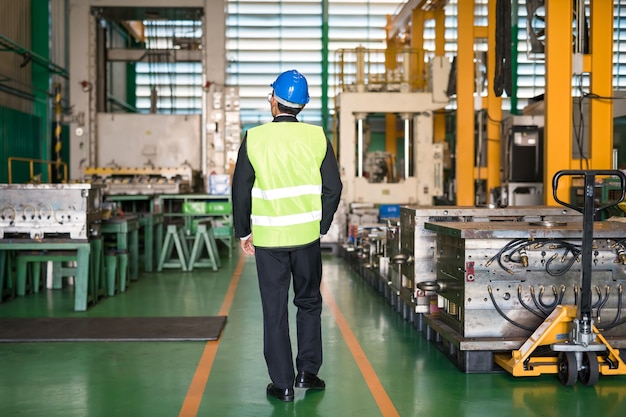 제조 창고에서 현대 기계를 확인하기 위해 생산 부서를 따라 걷고 있는 안전모를 쓴 공장 관리자의 후면. 산업 비즈니스 개념입니다.
