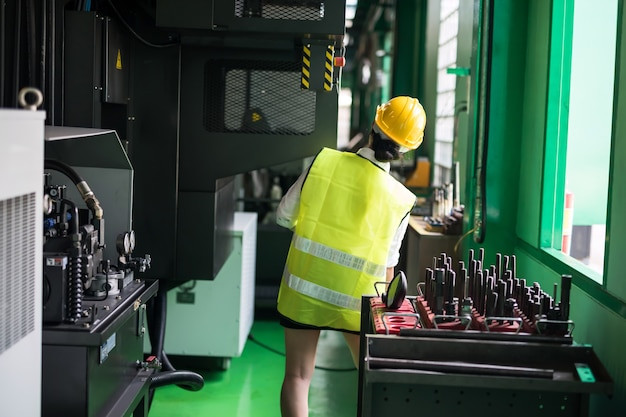 허리 위로 여성 검사의 후면은 전자 기계 및 나사 장비를 확인하기 위해 공장으로 걸어갑니다. 아시아 작업자는 안전 준비 및 품질 관리(qc)를 감사하기 위해 하드웨어를 검사합니다.