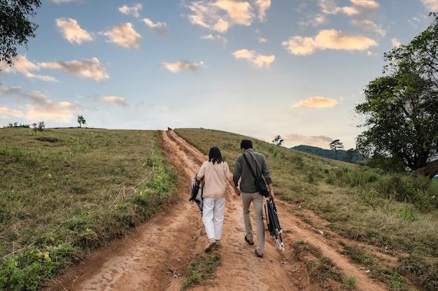 Задняя часть молодой азиатской пары, несущей стул и ткань, идущая на зеленом холме в сельской местности вечером