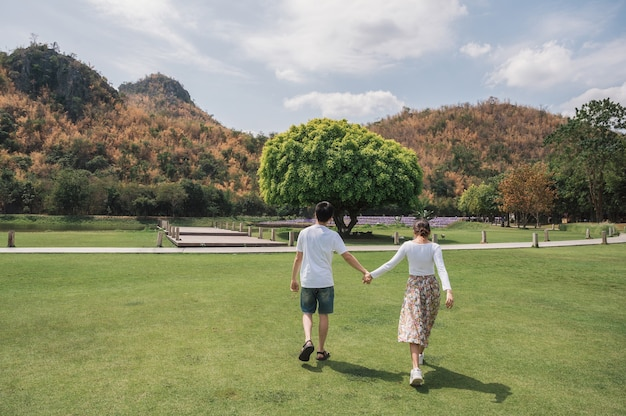 公園で草や大きな木の成長に手をつないで歩く若いアジアのカップルの後部