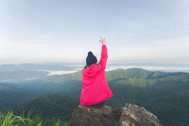 Задняя часть молодой женщины, сидящей на скале и вид на вершину горы