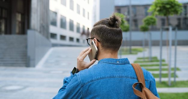 Сзади на кавказский молодой человек в очках гуляет по улице и разговаривает по мобильному телефону. красивый мужчина в рубашке очков и джинсов, говоря на внешнем мобильном телефоне. телефонный звонок разговор. вид сзади