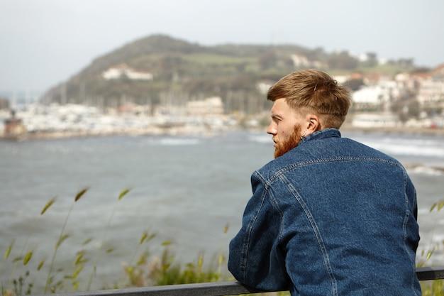 スタイリッシュな青を身に着けているハンサムな若いひげを生やした男のリアの肖像画