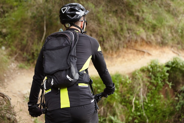 Rear shot of biker in black and yellow cycling clothing, helmet and backpack riding electric mountain bicycle on trail while training outdoors on weekend. people, healthy lifestyle and sports concept