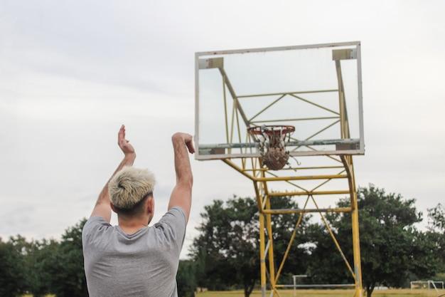 放棄されたバスケットボールコートにボールを投げる若い男のリアショット。