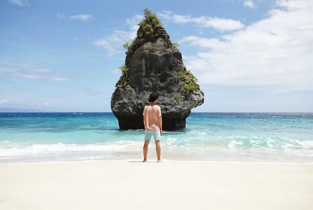 Задний снимок стильного молодого человека в модной черной шляпе, стоящего босиком на песчаном пляже перед скалистым утесом, ожидая неизвестной загадочной девушки, которую он случайно встретил и в которую влюбился