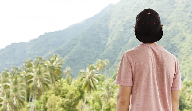 Задний снимок молодого кавказского путешественника, одетого в снэпбэк, который чувствует себя свободным и умиротворенным во время своего путешествия на летние каникулы