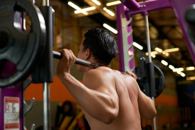 Rear side view of topless athlete lifting weight in the gym