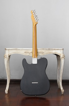 Rear telecaster electric guitar resting on antique table