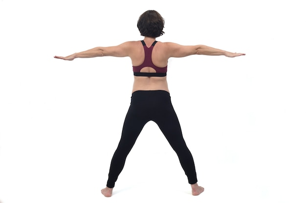 Вид сзади портрета беременной женщины, тренирующейся на белом