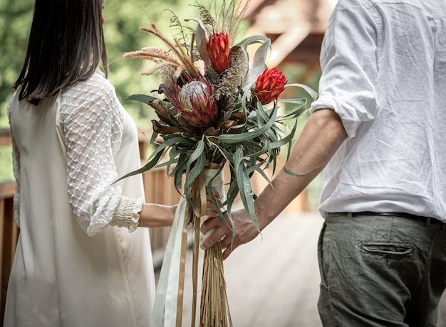 이국적인 프로테아 꽃으로 꽃다발을 들고 사랑에 빠진 부부의 뒷모습