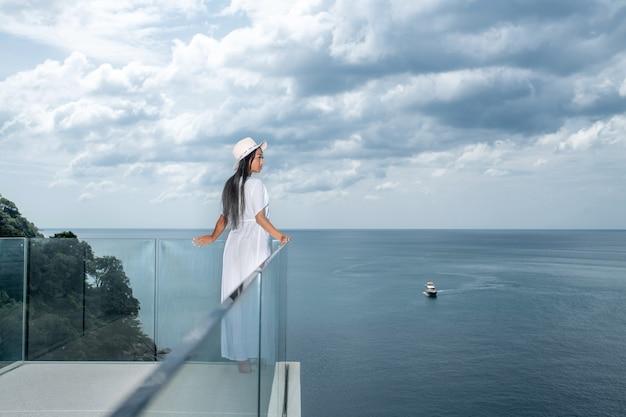 Вид сзади: потрясающая девушка в шляпе с длинными чёрными волосами стоит на прозрачной террасе и любуется видом на море с лодкой. тропический отдых. отдых и наслаждение