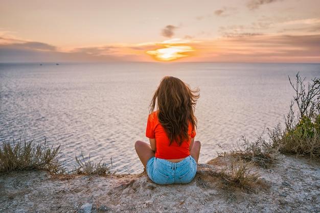 背面図若い女性が夕日と海の前の崖の端に座っています