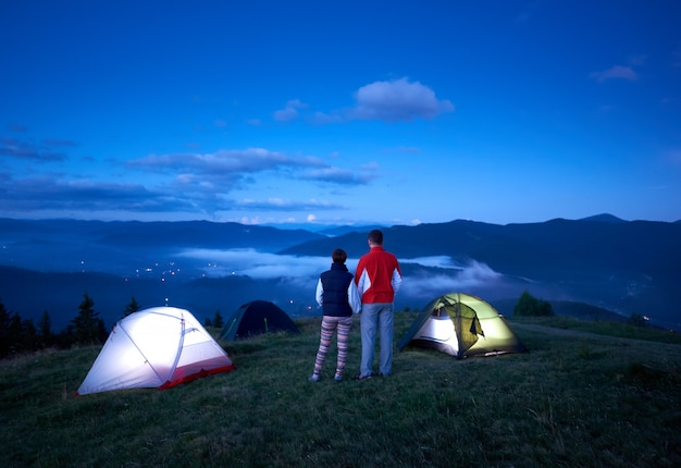 Вид сзади активные пары, взявшись за руки, наслаждаясь восходом солнца возле кемпинга в горах. туманные холмы и голубое небо создают красивый утренний пейзаж