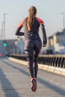 Rear view of active woman running