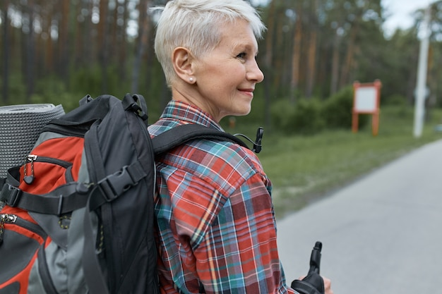 Rear view of adventurous middle aged woman with pixie haircut carrying backpack while hiking, going to spend weekends in mountains.