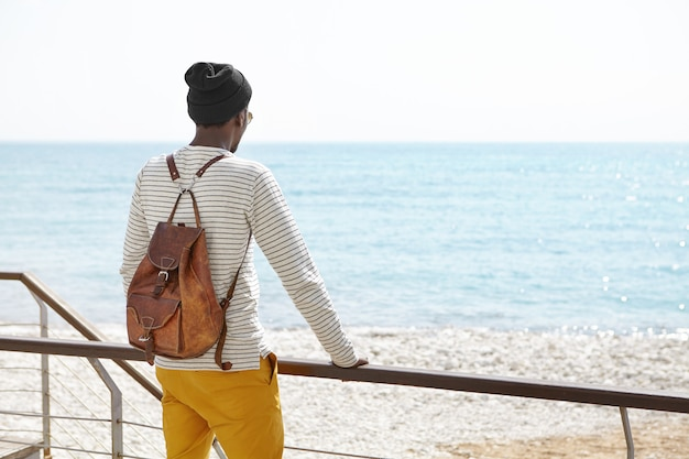 Rear view of african american male wearing hat and backpack, keeping hands on metal fence, came to urban beach on sunny day to relax, looking at sea and blue sky horizon
