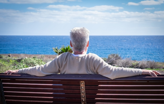 Rear view of an aged white-haired man relaxing in front to the sea, sitting on a bench looking at the horizon. senior man enjoying retirement
