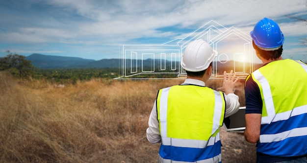 Люди осмотра инженера архитектора вида сзади стоя напольные и держа таблетку на строительной площадке. многонациональный бизнес-менеджер смотрит в будущее с планом строительства. инженерная концепция