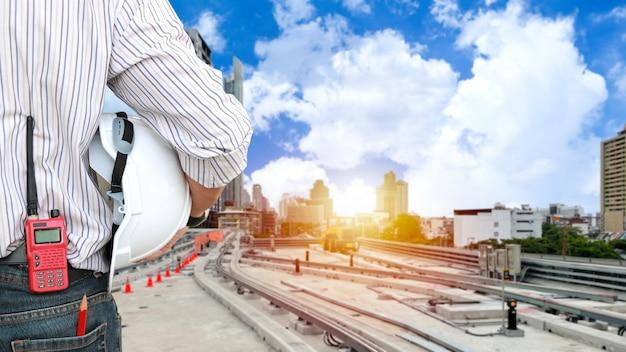 後ろ姿の建築家の男性が立って鉄道建設をチェックし、ヘルメットをかぶってスカイトレインに取り組んでいます。建物と街並みの背景を持つ将来を見据えたアジアのビジネスマネージャー。