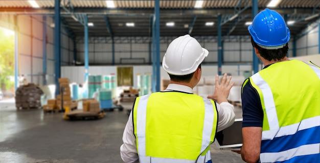 Люди архитектора вида сзади и рабочий стоя и проверяя большой склад с компьютером. многонациональный бизнес-менеджер смотрит в будущее со складским зданием.