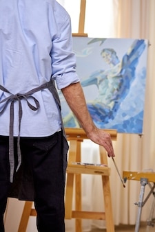 Rear view on artist man holding paintbrush in hands and looking at canvas, view from back