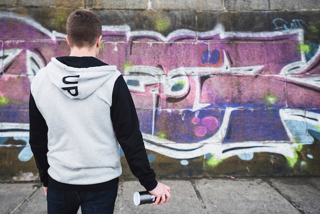 Rear view of a artist standing in front of graffiti wall