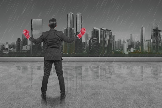 Rear view of asian businessman with red boxing gloves with rainy background