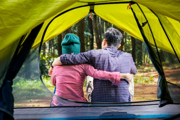 Rear view of asian couple sitting on the outside tent
