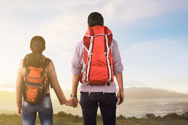 Rear view of asian couple with backpack looking at mountain view with a blue sky. world tourism day