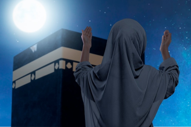 Rear view of asian muslim little girl in a veil standing and raised hands praying in front of the kaaba with the night scene background