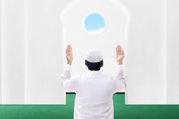 Rear view of asian muslim man sitting while raised hands and praying on the mosque