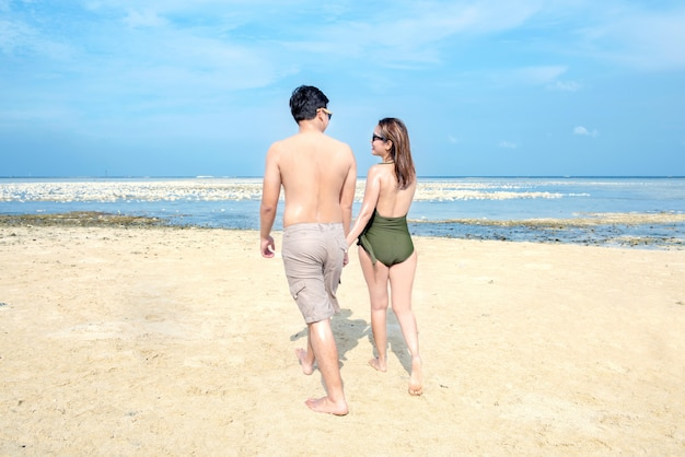 Rear view of asian romantic couple relax and walking on the beach