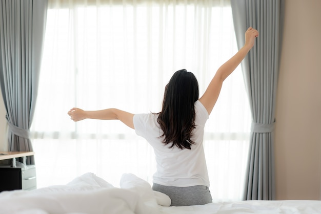 Rear view of asian woman stretching hands and body in bed after wake up in bedroom at home. concept for start new day with happiness. copyspace on the left. young happy working female life