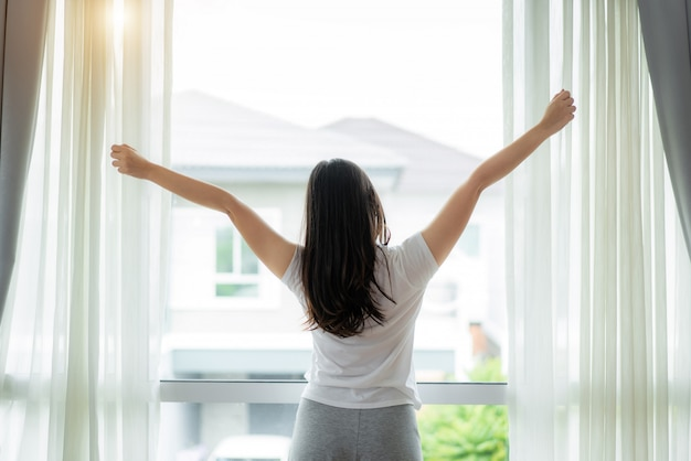 Rear view of asian woman stretching hands and body near window after wake up in bedroom at home. concept for start new day with happiness. young happy working female life