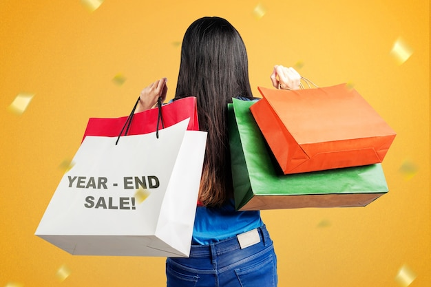 Rear view of asian woman with shopping bags after shopping on year-end sale. happy new year 2021