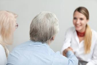 年配のカップルハンドシェイクアドバイザーまたは医療従事者の背面図