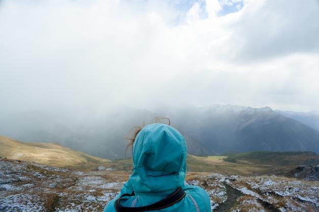 후드를 입은 여성의 뒷모습은 알파인 산 앞에 있습니다. 야외에서 신선한 공기를 호흡하는 여성