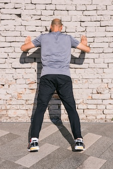 Rear view of athlete man leaning on brick wall while doing exercise
