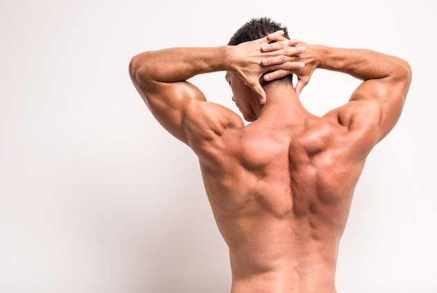 Rear view of athletic man is showing muscles.