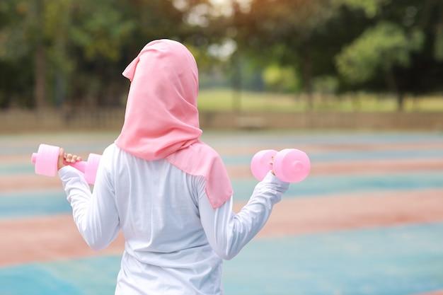후면보기 운동복 서 아침 운동을 위해 야외 아령 운동 젊은 아시아 무슬림 여성. 활성 소녀 녹색 나무 배경으로 팔 뚝 운동에 운동. 스포츠 컨셉