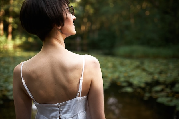 Rear view of attractive dark haired woman with short haircut posing in forest wearing eyeglasses and white strap dress standing by pond, enjoying calm peaceful atmosphere.