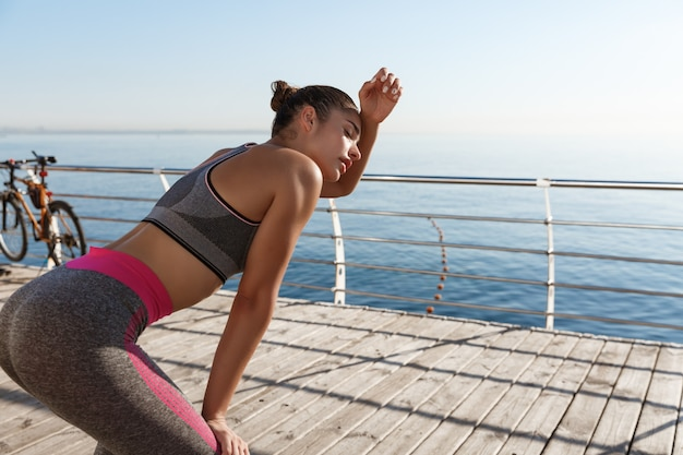 Rear view of attractive fitness woman taking a breath after jogging along seaside