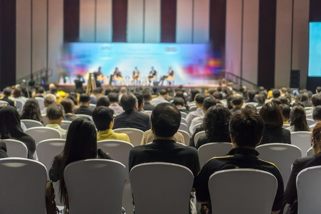 Rear view of audience listening speakers on the stage in the conference hall or seminar meeting