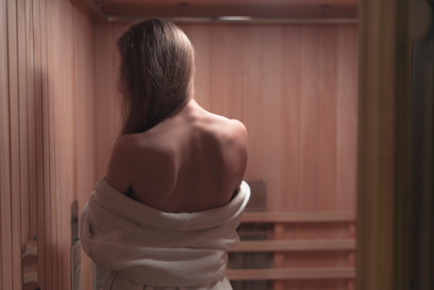 Rear view of backless sexy young woman in sauna