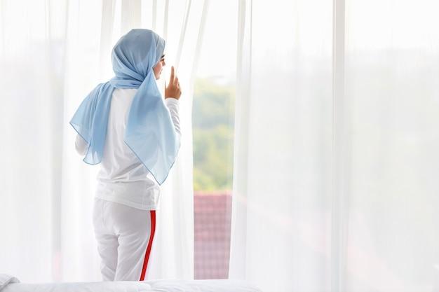 Вид сзади красивая азиатская арабская женщина в белом пижаме смотрит в сторону от окна