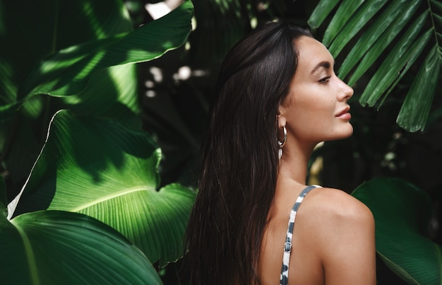 Rear view of beautiful brunette woman with golden tan, wearing a bikini, standing in profile in green leaves.