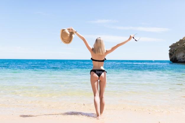 La retrovisione di bella giovane donna ha alzato le sue mani alla spiaggia